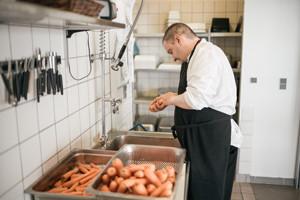 kantinen-5-15-portræt-køkkenmedarbejder-skræller-gulerødder